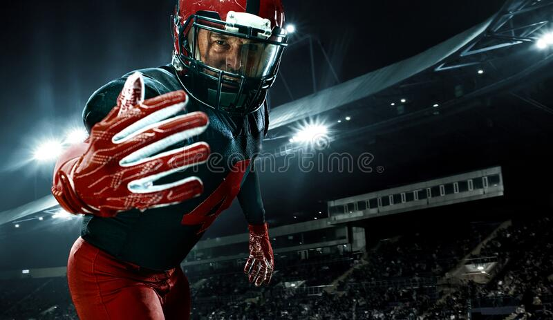 Closeup portrait of american football player, athlete sportsman in red helmet on grand arena background. Sport and royalty free stock photos