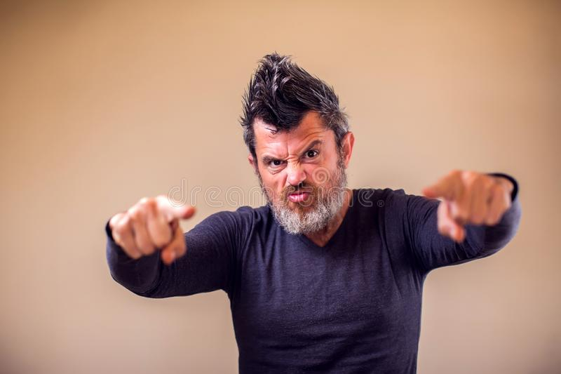 Closeup portrait of an angry adult man with a beard and iroquois poins with fingers at camera. People, emotions concept. Closeup portrait of an angry adult man royalty free stock images