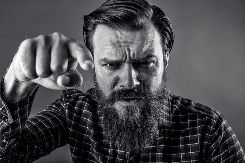 Closeup portrait of an angry bearded man threatening with his fist stock images