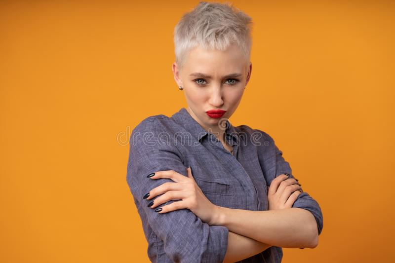 Closeup portrait of an angry girl isolated on the orange background stock photo