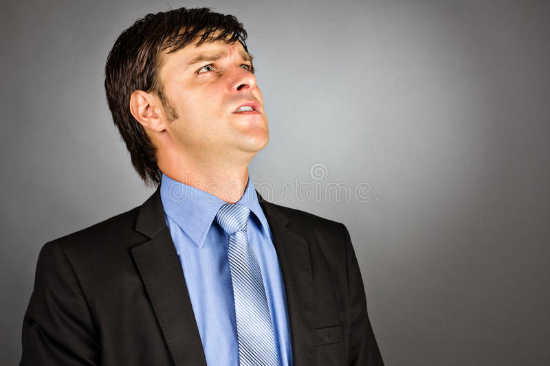 Closeup portrait of an angry young businessman looking up stock image