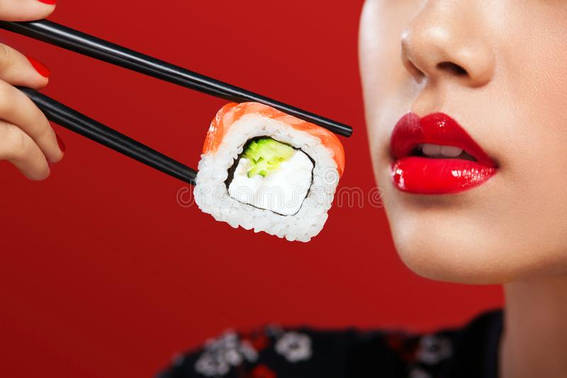 Closeup portrait of Asian woman with sushi eating sushi and rolls on a red background. Black Friday sushi sale. stock image