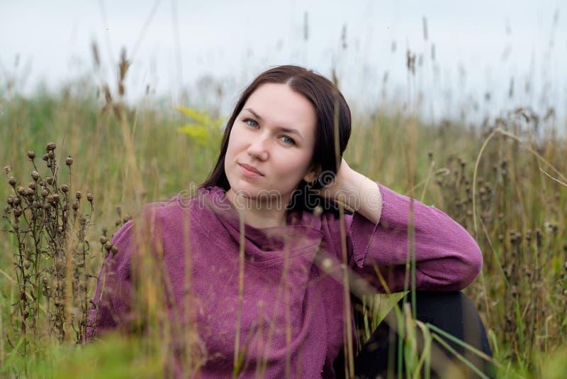 Closeup portrait of attractive brunette female on autumn floral field. stock images