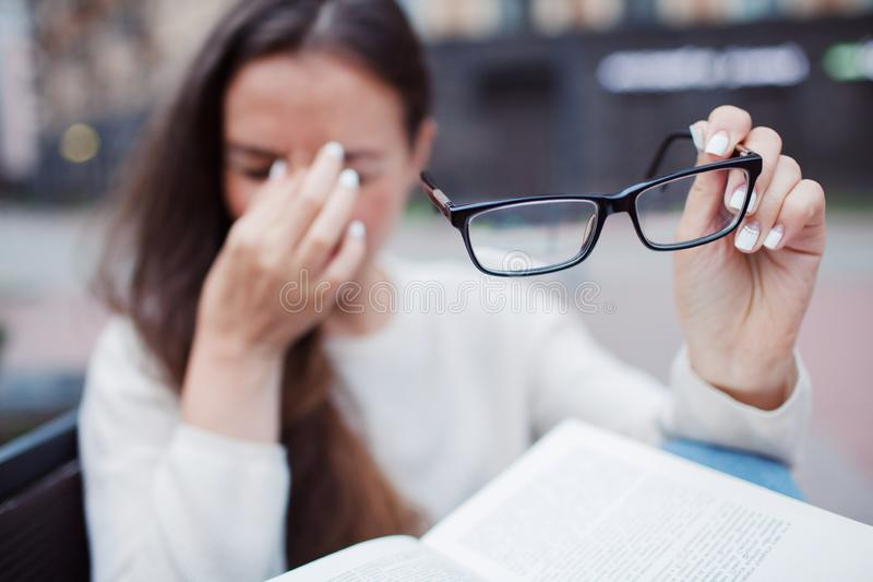 Closeup portrait of attractive female with eyeglasses in hand. Poor young girl has issues with vision. She rubs her nose and eyes royalty free stock images