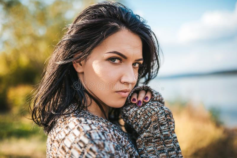 Closeup portrait of attractive woman relaxing and enjoying nature. Caucasian dreamy female looking at the camera and wearing stock image
