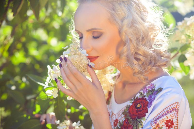 Closeup portrait of attractive young blonde woman with makeup and curly hairstyle in stylish floral dress standing and holding stock images