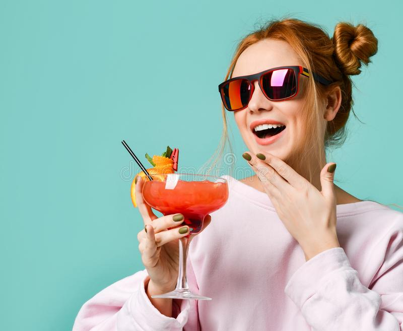 Closeup portrait of Bartender woman with strawberry margarita cocktail in hand in red sunglasses stock images