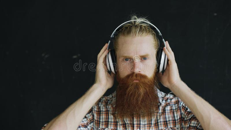 Closeup portrait of bearded young man in headphones listen to music and looking into camera smiling royalty free stock images