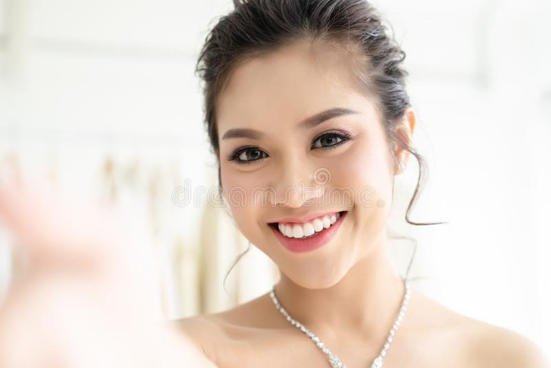Closeup portrait of beautiful Asian woman in elegant white wedding dress taking a selfie in wedding atelier royalty free stock images