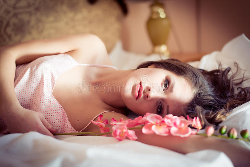Closeup portrait of beautiful attractive brunette woman lying in bed with a flower orchid on hand & looking at camera royalty free stock image