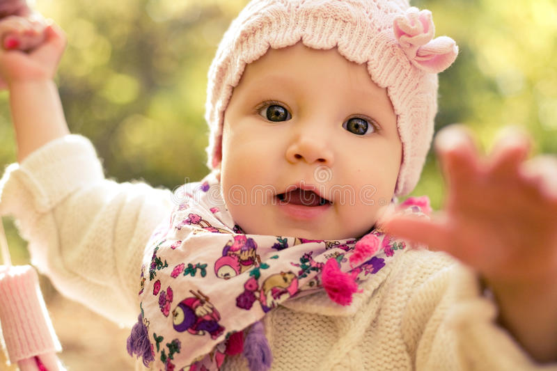 Closeup portrait of beautiful baby girl wearing stylish hat and cozy sweater. Outdoors spring, autumn photo. royalty free stock image