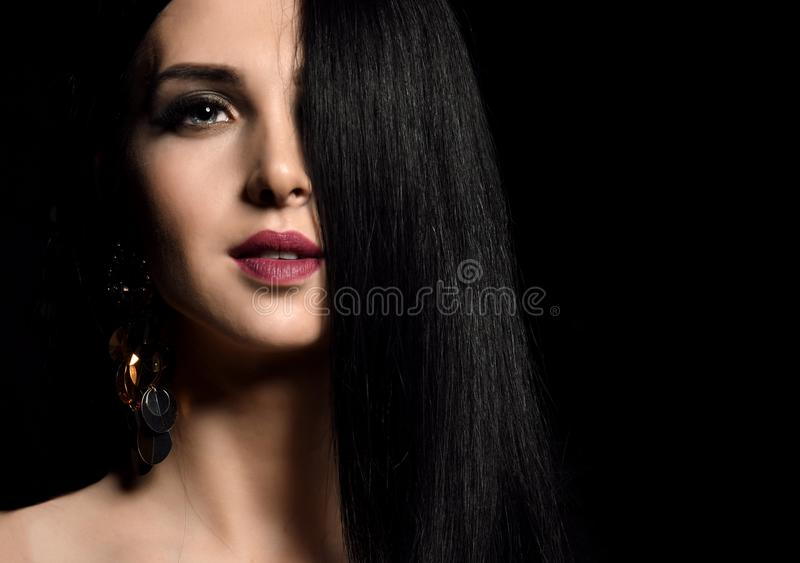 Closeup portrait of beautiful brunette girl with healthy long hair on black royalty free stock photo
