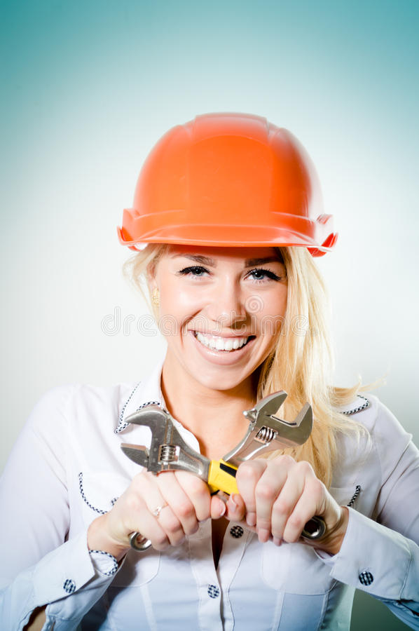 closeup portrait of beautiful charming young woman happy smiling in a helmet with two wrench royalty free stock image