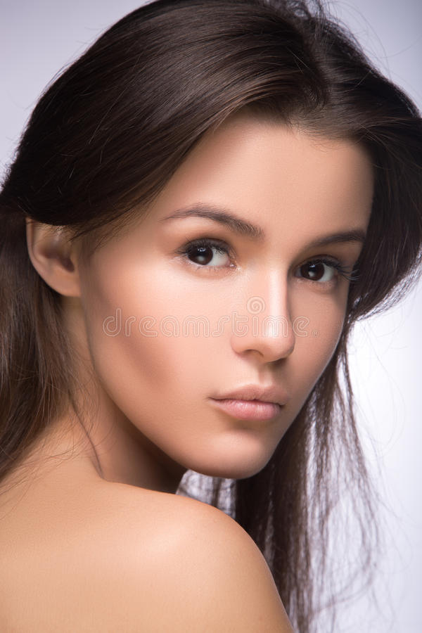 Closeup portrait of beautiful girl with clear healthy skin. Looking at the camera over shoulder. perfect fashion model studio stock photos