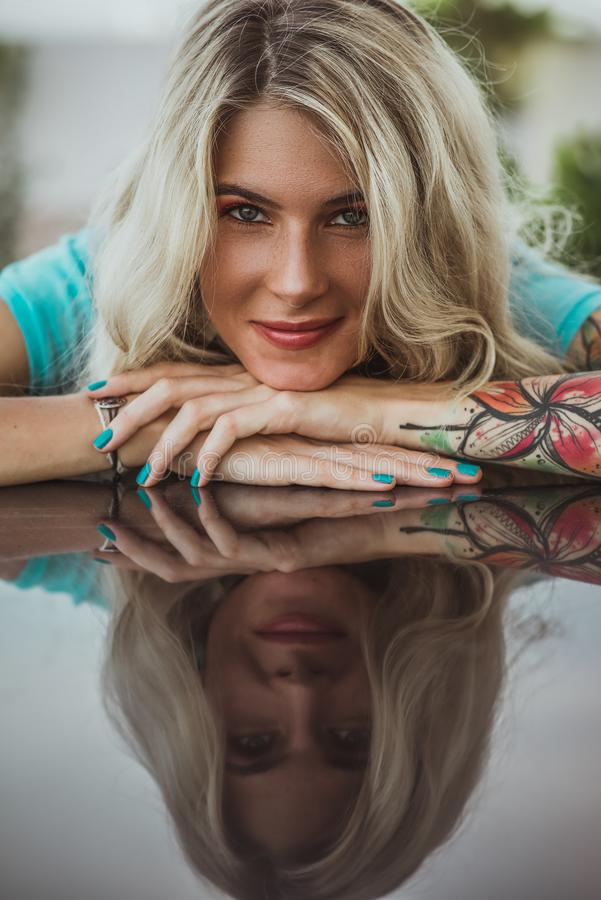 Closeup portrait of. Beautiful girl put her head in her arms with tattoos. expectation. stock images