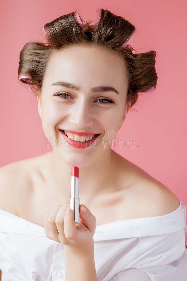 Closeup portrait of beautiful girl putting on red lipstick royalty free stock photography