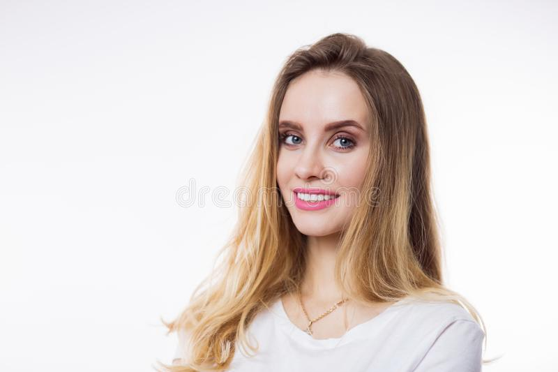 Closeup portrait of beautiful happy young woman with blonde hair and looking at camera on white background royalty free stock images