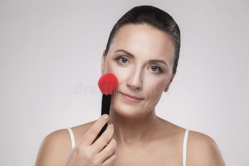 Closeup portrait of a beautiful middle aged woman applying dry cosmetic tonal foundation on the face using makeup brush, isolated stock images