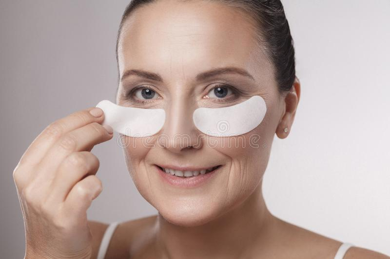 Closeup portrait of beautiful middle aged woman with perfect skin using white hydrogel patches with lifting anti-wrinkle collagen stock photo