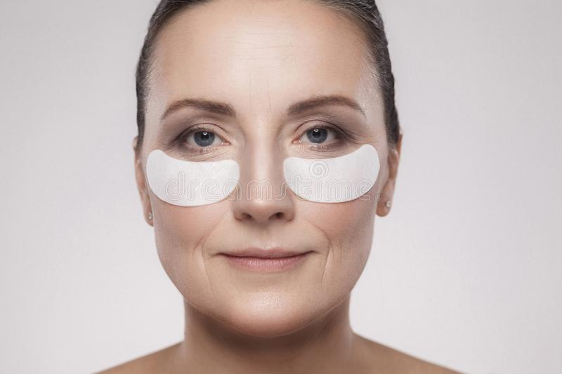 Closeup portrait of beautiful middle aged woman with perfect skin using white hydrogel patches with lifting anti-wrinkle collagen stock photography
