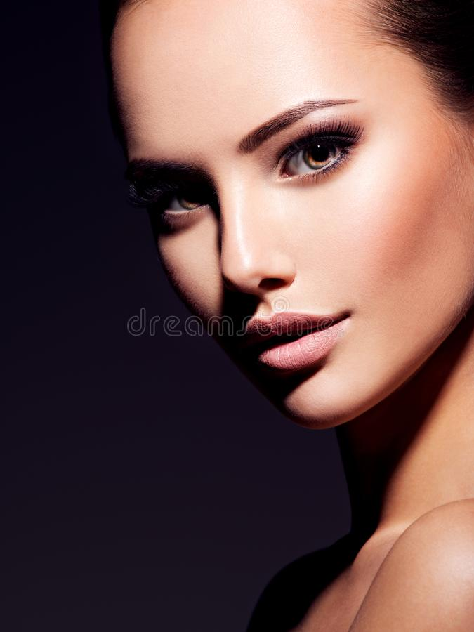 Close-up face of a beautiful sexy woman with brown make-up of  eyes. Closeup portrait of a beautiful sexy fashion woman with glamour makeup posing at studio stock image