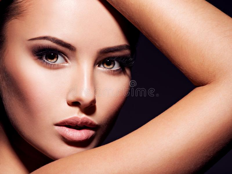 Close-up face of a beautiful sexy woman with brown make-up of  eyes. Closeup portrait of a beautiful sexy fashion woman with glamour makeup posing at studio stock photography