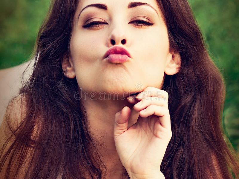 Closeup portrait of beautiful sexy woman with red lips giving kiss sign lying on green grass outdoors royalty free stock image