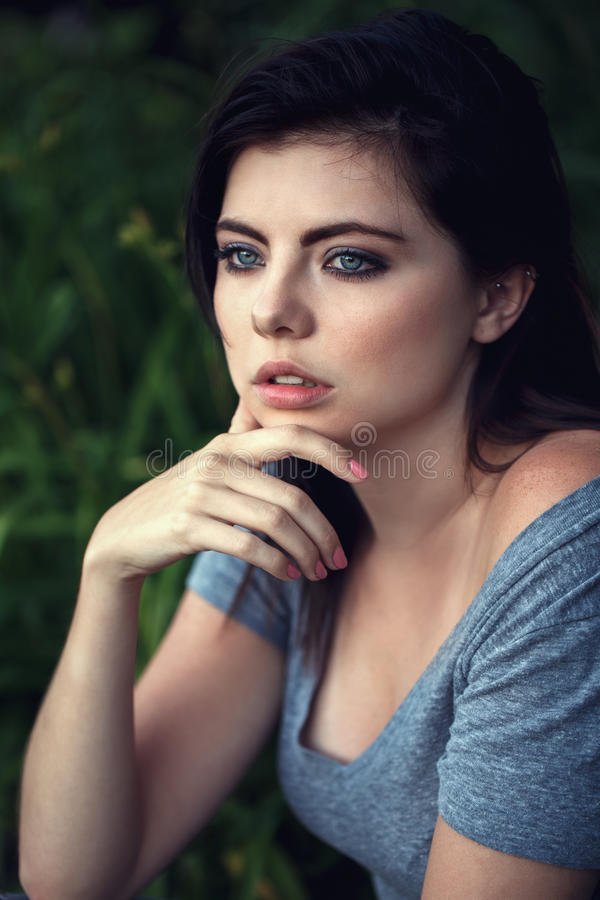 Closeup portrait of beautiful young Caucasian woman with black hair, blue eyes, looking away stock photo