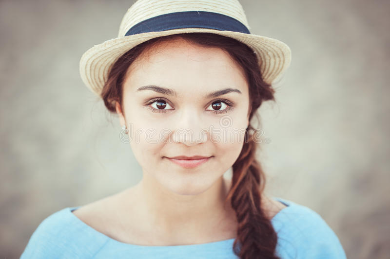 Closeup portrait of beautiful smiling white Caucasian brunette girl with brown eyes and plait, in blue dress and straw hat. Looking in camera, rustic retro stock photo