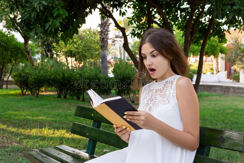 Closeup portrait of a beautiful surprised girl with wide opened eyes who is reading a book on the bench in the park. Human emotion stock photography