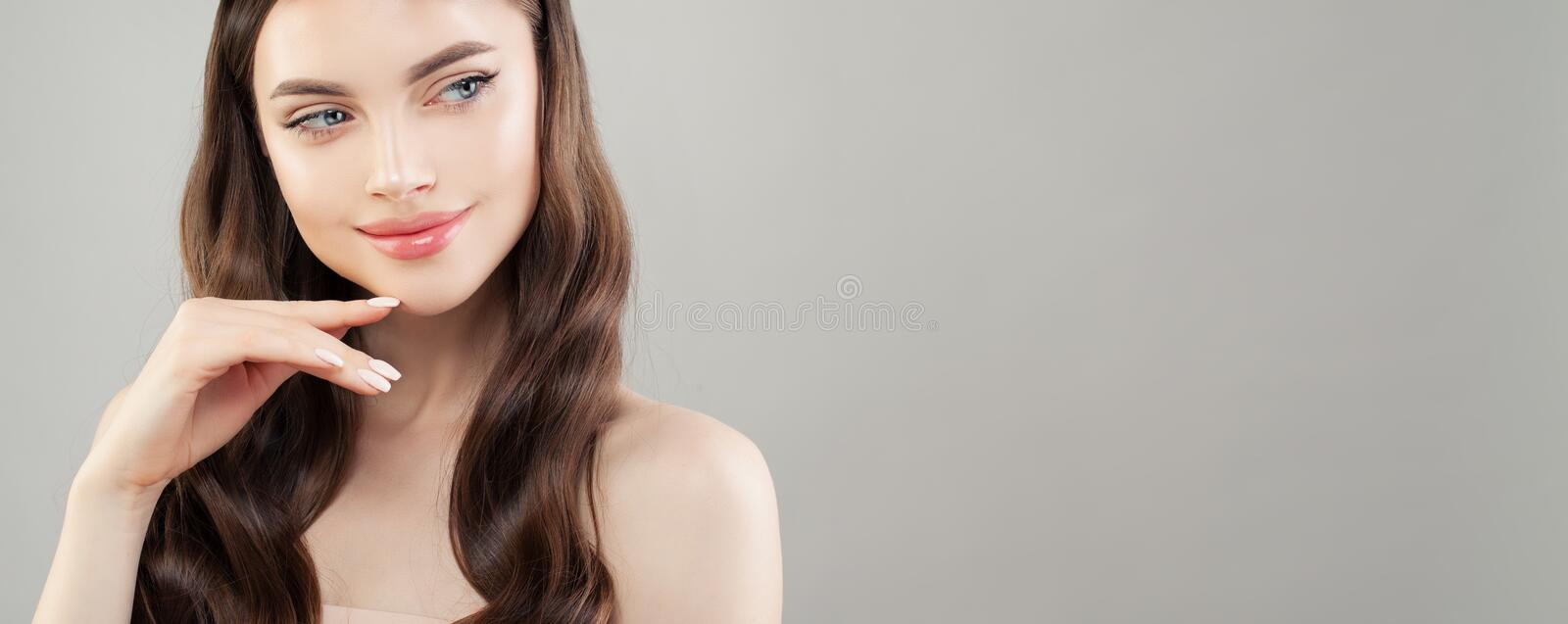 Closeup portrait of beautiful woman with clear skin smiling and looking aside on gray banner background.  royalty free stock photography