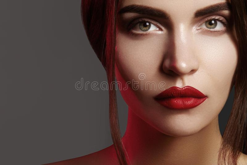 Closeup portrait with of beautiful woman face. Red color of fashion lip makeup, clean shiny skin and strong eyebrows royalty free stock images