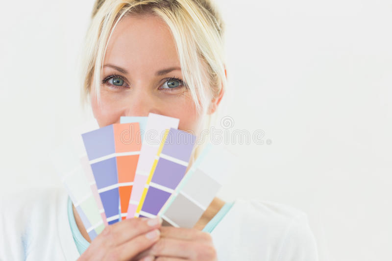 Closeup portrait of a beautiful woman holding color swatches royalty free stock photos