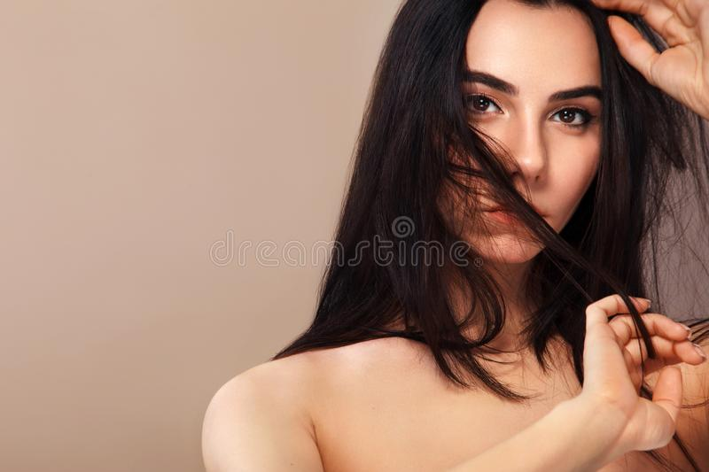 Closeup portrait of a beautiful woman. Pretty face of the young adult girl. Fashion model posing at studio. Cosmetics royalty free stock photography
