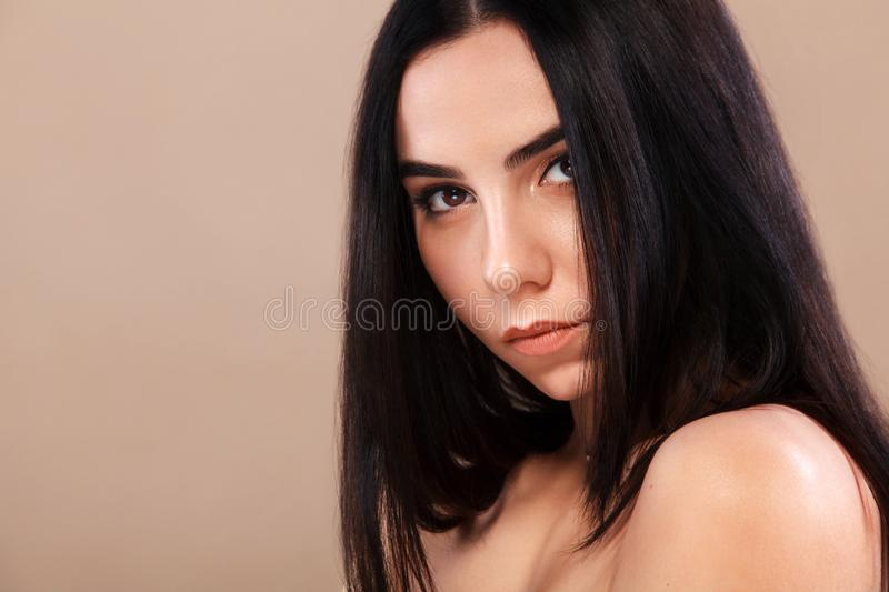 Closeup portrait of a beautiful woman. Pretty face of the young adult girl. Fashion model posing at studio. Cosmetology royalty free stock images