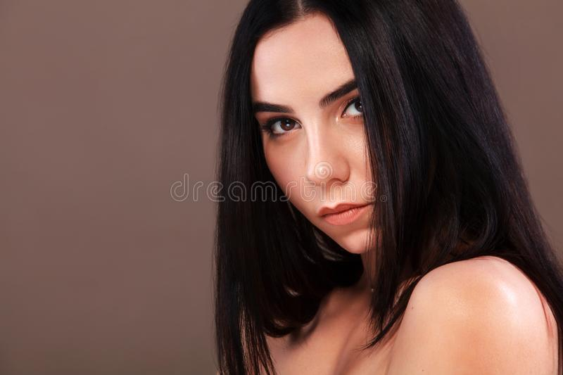 Closeup portrait of a beautiful woman. Pretty face of the young adult girl. Fashion model posing at studio. Cosmetology stock image