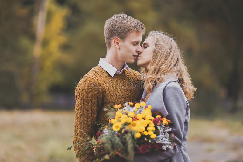 Closeup portrait of beautiful young couple kisses, love each oth. Young girl and guy with blond hair kiss, show love, affection. Boy and girl of European stock photography