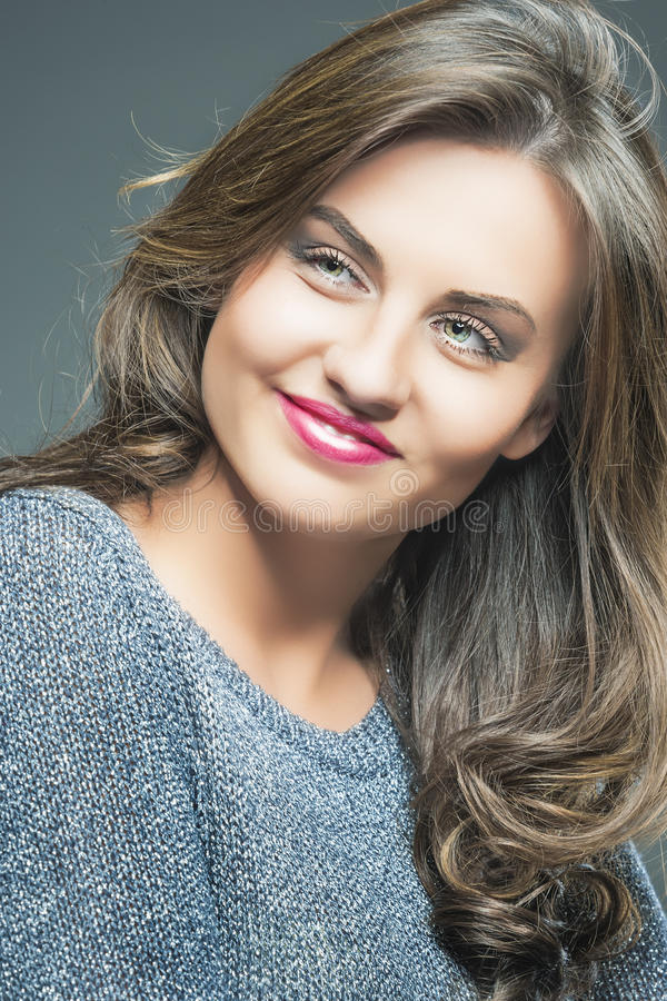 Closeup Portrait of a Beautiful Young Female with Brown Long Hair and Fashion Make up Smiling. Against Gray. Vertical Image royalty free stock photos