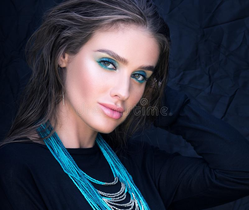 Closeup portrait of beautiful young woman in black. Professional makeup and hairstyle stock images