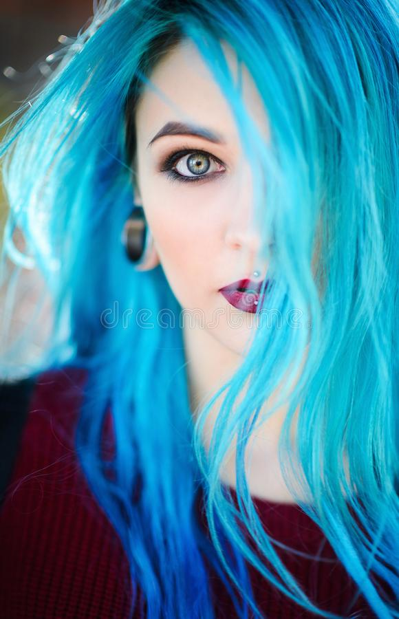 Closeup portrait of beautiful young woman with blue hair royalty free stock image