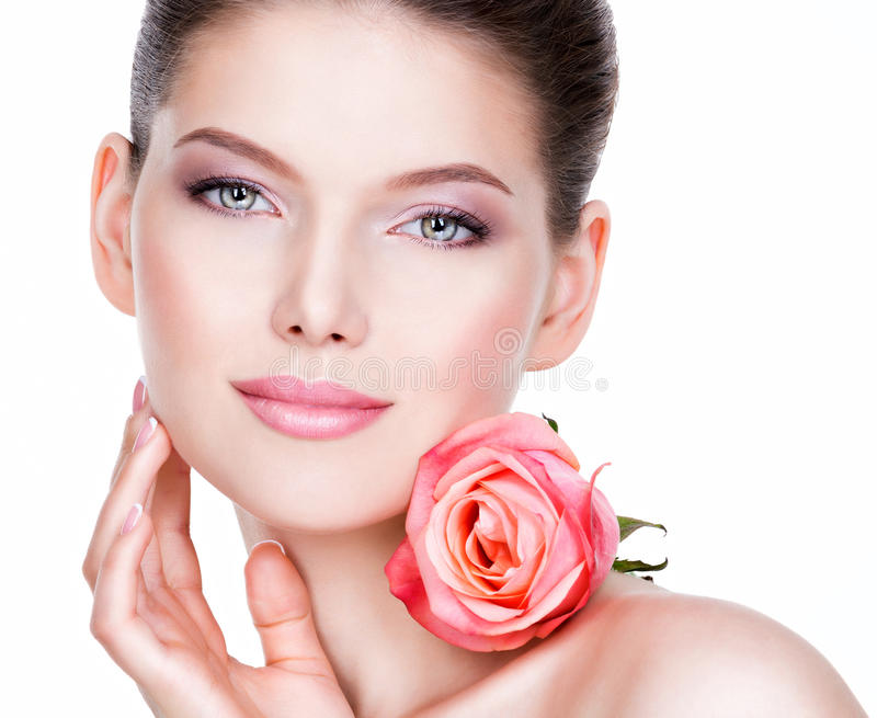 Closeup portrait of beautiful young woman with flower near face. royalty free stock images
