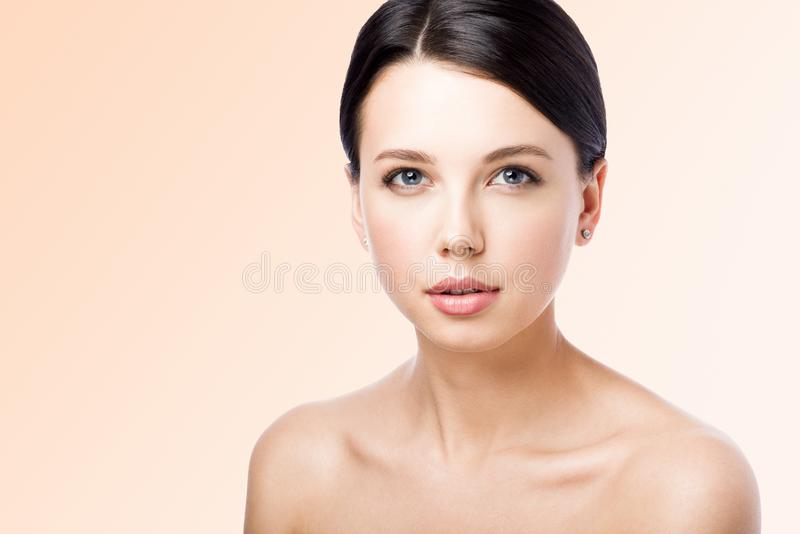 Closeup portrait of beautiful young woman on light beige background stock photography