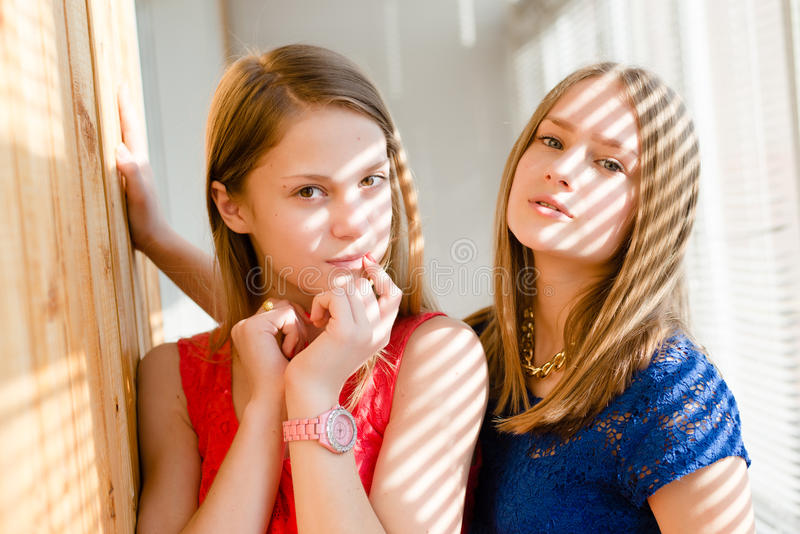 Closeup portrait of 2 best girl friends or sisters beautiful blond young women having fun posing looking at camera on sun lighted stock photo
