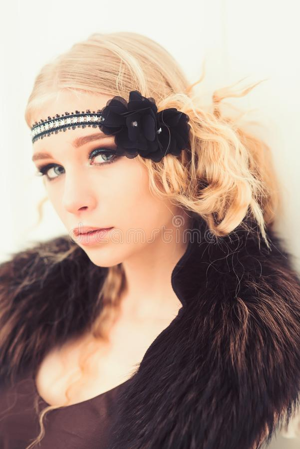 Closeup portrait of blond actress playing in 1920s movie. Pretty girl in headband and fur collar isolated in white royalty free stock photos