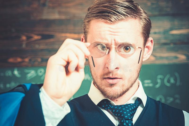 Closeup portrait of blond guy holding glasses with magnifying lenses in front of his eyes. Gentleman with perfect stock photo