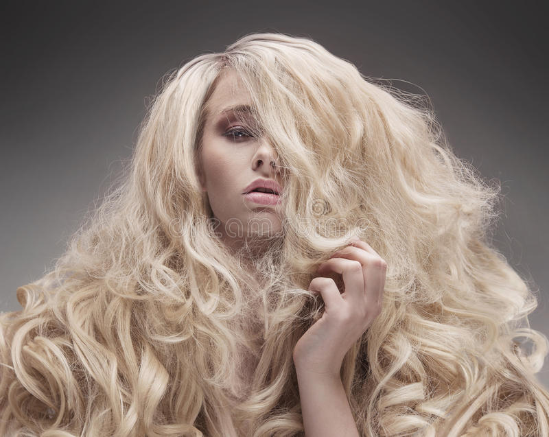 Closeup portrait of a blonde with a fluffy, curly hairstyle stock photo