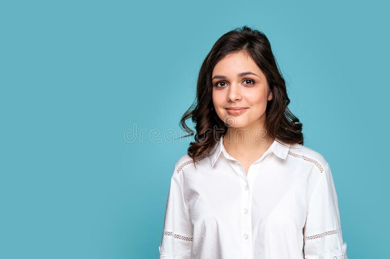 Closeup portrait of brunette beautiful girl in a white blouse isolated over the blue background. stock photo