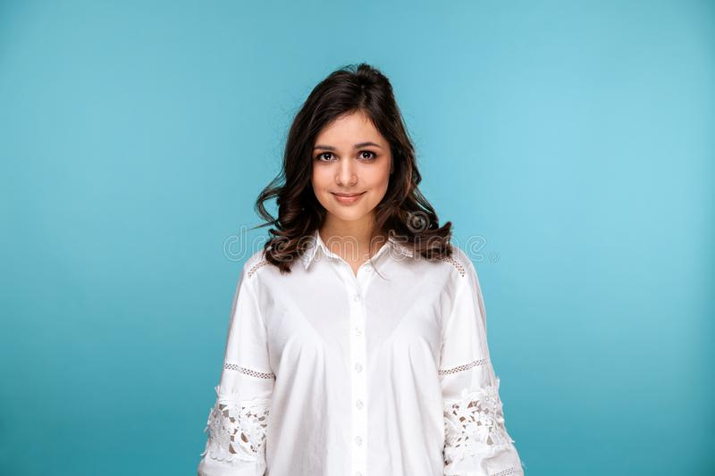 Closeup portrait of brunette beautiful girl in a white blouse isolated over the blue background. stock images