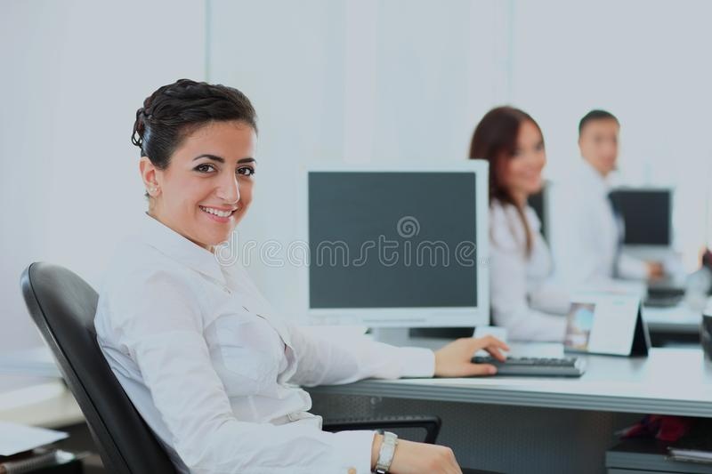 Closeup portrait of business woman giving you cute smile with colleagues in background. royalty free stock image