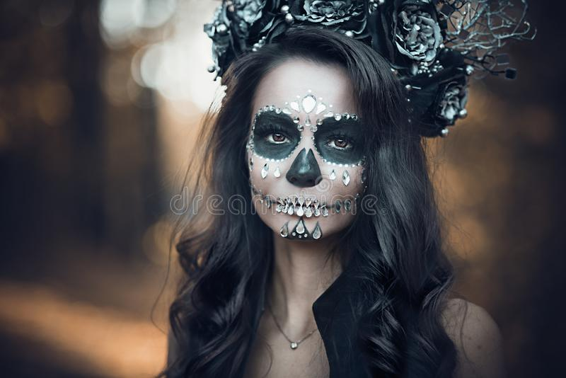 Closeup portrait of Calavera Catrina in black dress. Sugar skull makeup. Dia de los muertos. Day of The Dead. Halloween.  stock photo